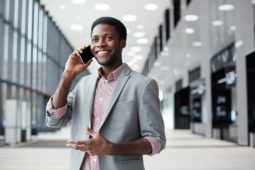Happy African-american businessman talking by smartphone in large airport lounge
