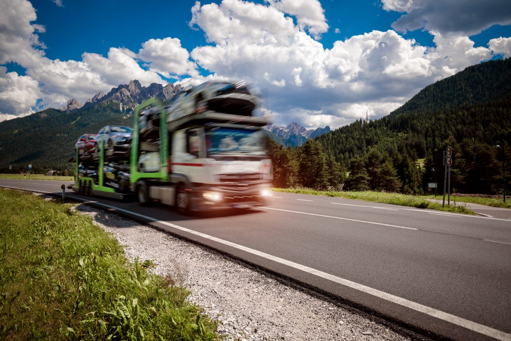 Truck trailer transports new cars rides on highway, Italy natural landscape Alps. Warning - authentic shooting there is a motion blur.