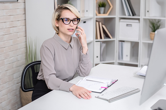 Portrait of blonde successful businesswoman speaking by mobile  phone sitting at desk in modern office and talking to client