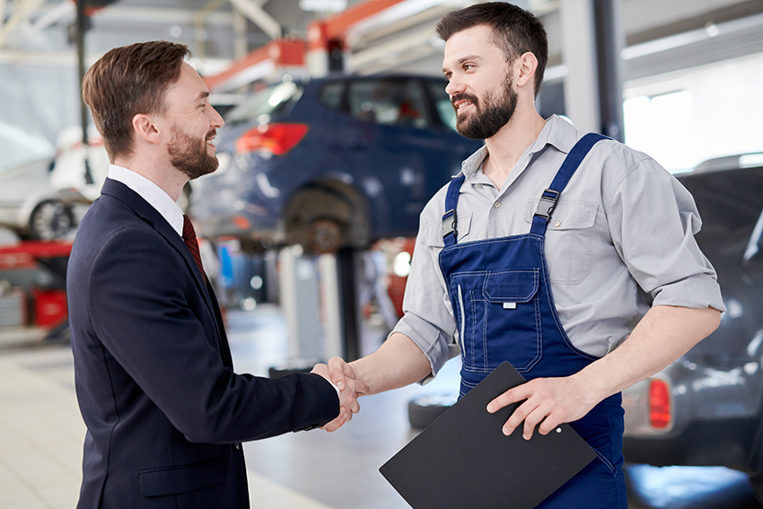Side view portrait of smiling handsome businessman shaking hands with  bearded mechanic standing in car service and repair center, copy space