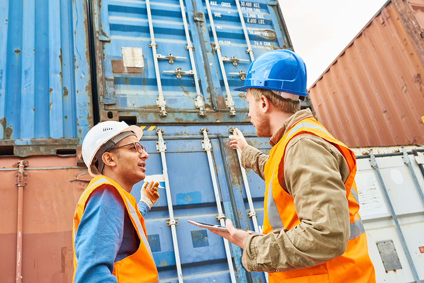 Two confident supervisors wearing reflective vests and hardhats discussing details of    loading ship with container storage units while gathered together in port